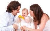 mom dad and baby with flower